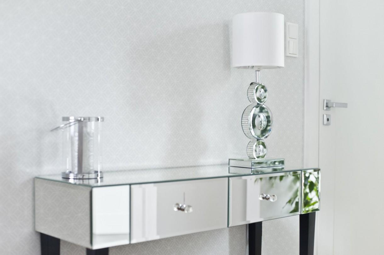 Domy i mieszkania, Ponadczasowe wnętrze w stylu modern classic - Z jadalni już tylko krok do urządzonej na wskroś nowocześnie kuchni. Czysta biel podłogi, ścian i prostych szafek sprawia, że wnętrze wydaje się bardziej przestronne. Wrażenie to dodatkowo potęgują przeszklone fronty szafek umieszczonych w kuchennym półwyspie od strony salonu. Uroku dodaje kuchni mozaika w stylu glamour na ścianie ponad blatem. Błyszczące, biało-szaro-czarne kostki pięknie odbijają dzienne światło, wpadające do środka przez duże okno w narożniku.